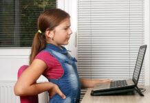 Ból pleców u dziecka - siedząca przy komputerze dziewczynka trzymająca się za bolące plecy