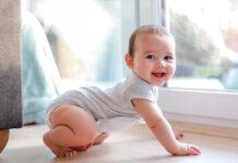 Raczkowanie – uśmiechnięte niemowlę na drewnianej podłodze w domu
